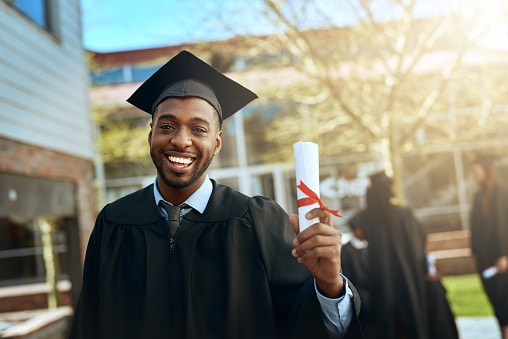 young man holding diploma in graduation outfit