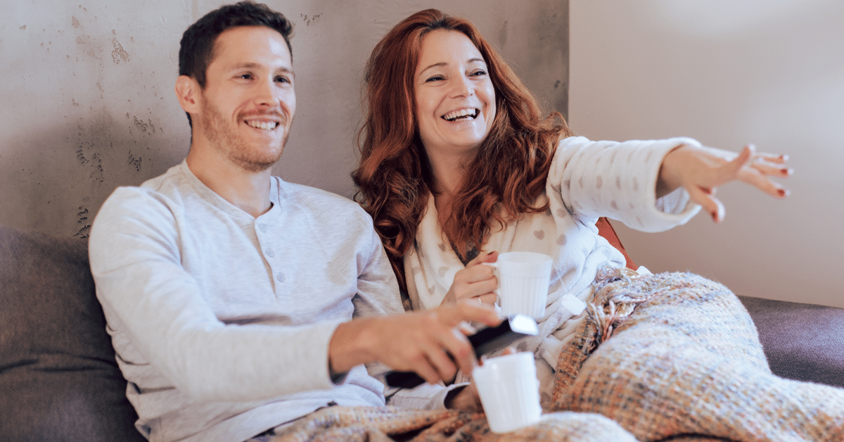 image of man and woman watching tv. The woman is pointing towards the right.