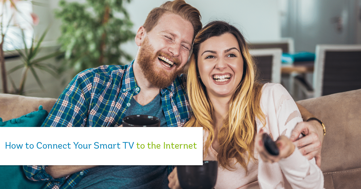 man and woman sitting on the couch laughing at tv