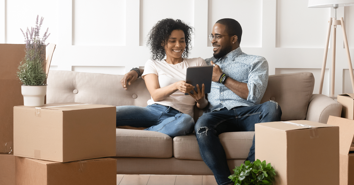 Man and woman sitting on a couch looking at tablet surrounded by boxes.