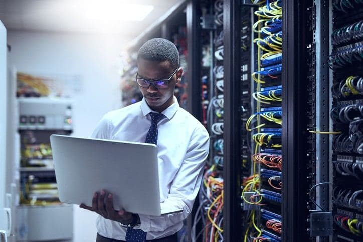 man in data centre with laptop